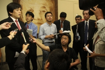 Mr. Joe Nakano answers questions while being surrounded by Japanese Press