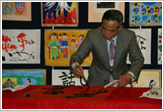 "Mr. Kimata, master calligrapher, paints the message ""To encounter people creates the light of friendship."""